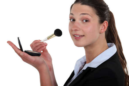 Businesswoman applying makeup Stock Photo - 16548148