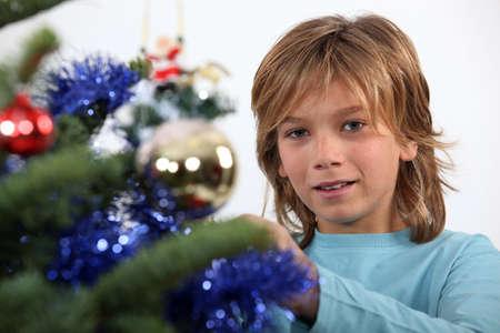 Prepubescent boy decorating a Christmas tree photo