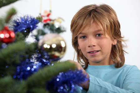 10 15 years: Prepubescent boy decorating a Christmas tree