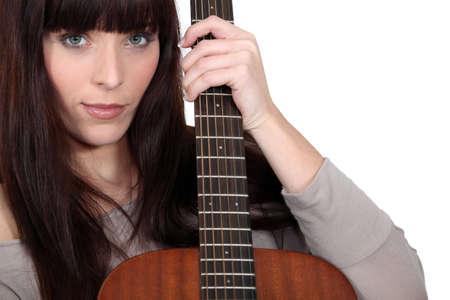 virtuoso: Brunette holding acoustic guitar