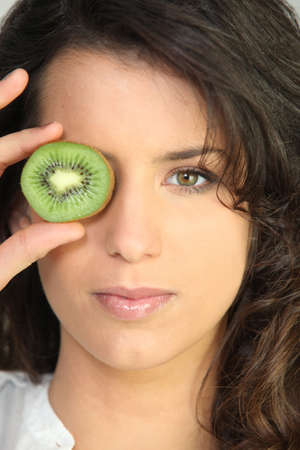 Young woman holding a kiwi photo