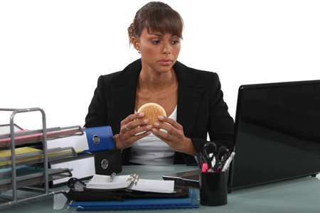 simultaneously: Woman eating a hamburger at her desk