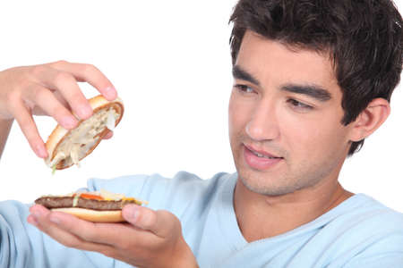 inspecting: Man opening a hamburger