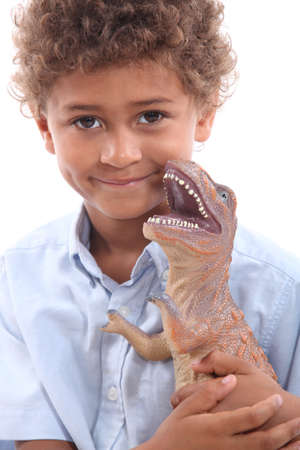 Little boy playing with toy dinosaur photo