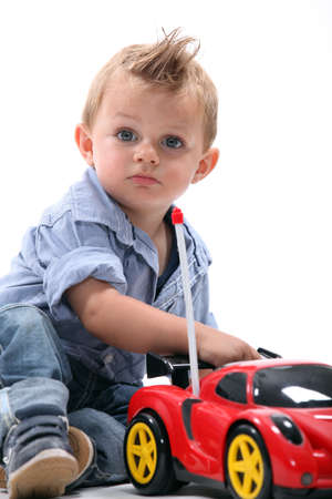 little boy playing with toy car photo