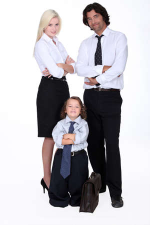 two parents: Man and woman in smart suit and little boy dressed as a businessman