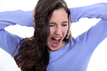 young woman plugging her ears and screaming photo