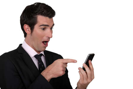 Surprised man pointing to his mobile phone photo