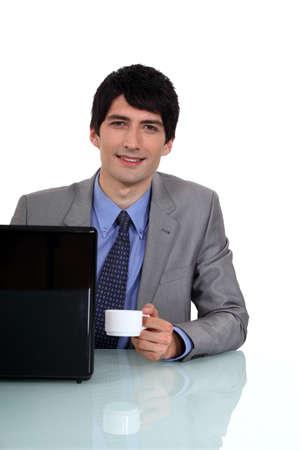 Businessman sat at desk drinking an espresso Stock Photo - 16546888