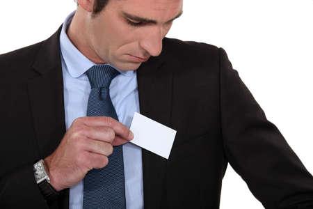 El hombre pone una tarjeta de visita en el bolsillo