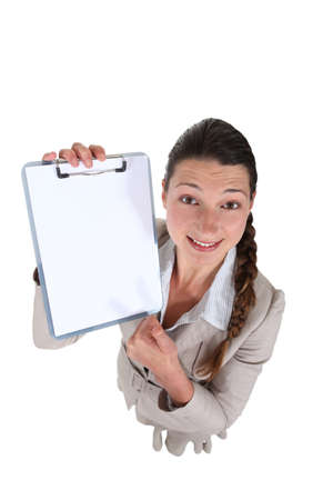 Brunette eagerly showing off clip-board Stock Photo - 16547067