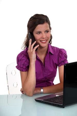secretary desk: Brunette secretary speaking in the phone