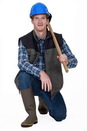 sledgehammer: Worker kneeling with sledge-hammer over shoulder