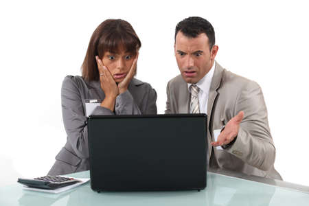annoy: A couple of businesspeople getting bad news  Stock Photo