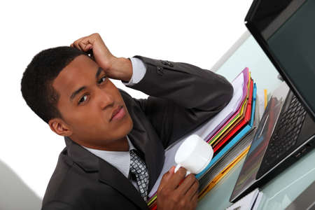 Tired young businessman with a coffee at his computer Stock Photo - 16554263