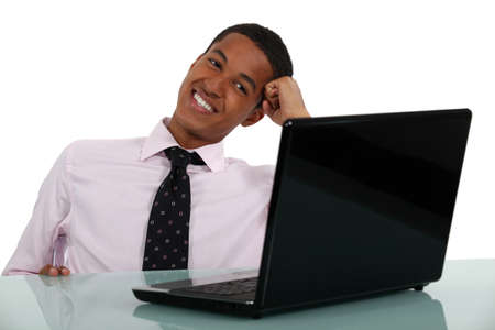 man using computer: Happy businessman sat at his desk Stock Photo