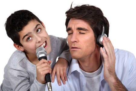 Father and son singing into a microphone photo