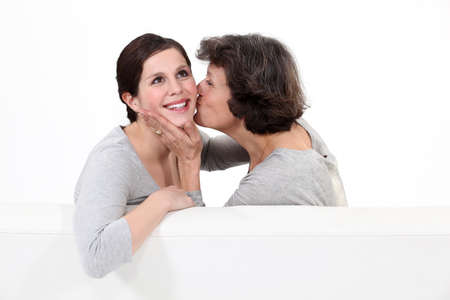 endearment: Mother kissing her daughter