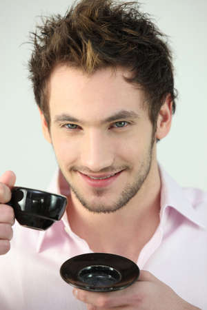 spiked hair: Smiling man drinking a cup of coffee