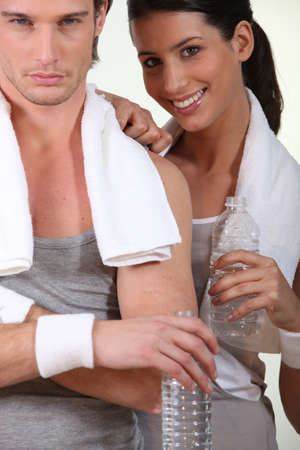 sportingly: Couple drinking water after hard gym work-out