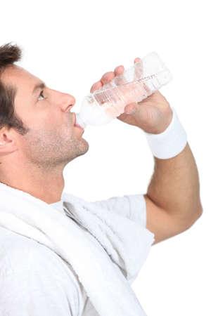 slurp: El hombre en ropa de gimnasia beber una botella de agua