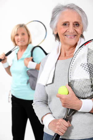 Two elderly women playing tennis photo