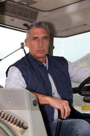 cosechadora: Granjero en la cabina de su tractor