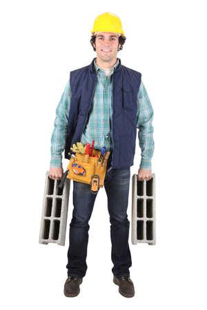 Smiling mason carrying cinder blocks photo