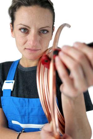 koperen leiding: Vrouwelijke loodgieter met koperen buis Stockfoto