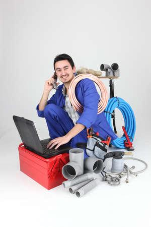 obrero: Labourer rodeado de herramientas y equipos Foto de archivo