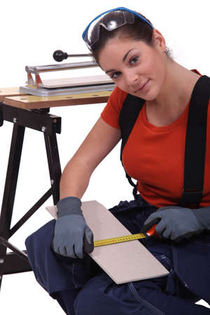 A woman measuring  a tile before cutting it  Stock Photo - 16670086