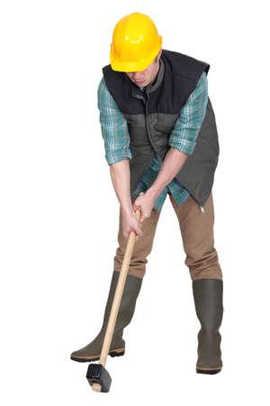 sledge hammer: Man trying to lift sledge-hammer