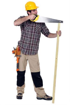 disregard: Tradesman carelessly sawing a plank of wood