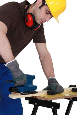 anti noise: falegname al lavoro con la macchina levigatrice