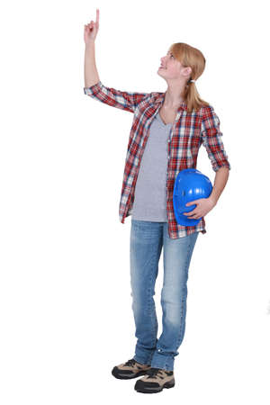 tradeswoman: Tradeswoman pointing to the ceiling Stock Photo