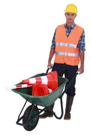holdup: Roadworker with cones in a wheelbarrow