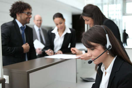 receptionist: Businesspeople crowding around the reception area of their company