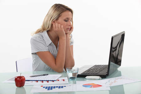 boring: Young woman pensive in front of laptop computer