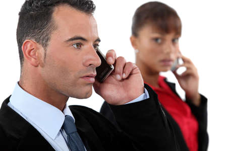 young businessman making a call and female colleague in background Stock Photo - 16669640