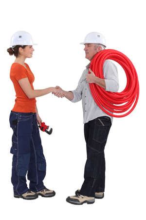 young female apprentice shaking hands with mature instructor photo
