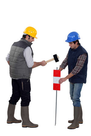 Two workers hammering sign into the ground Stock Photo - 16670788