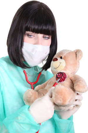 latex glove: Doctor listening to the heartbeat of a teddy bear Stock Photo