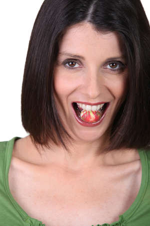 indulging: Woman eating candy Stock Photo