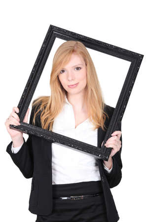 self conceit: Young woman putting herself in a picture frame