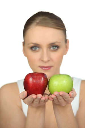 Blurry woman showing apples on white background photo