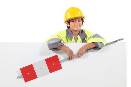 construction crew: little boy dressed as a road worker holding a traffic sign Stock Photo