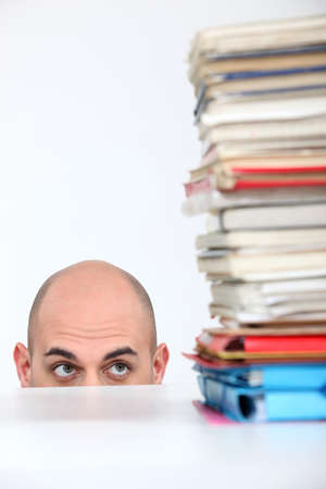 Man hiding behind a desk watching a stack of books Stock Photo - 16670329