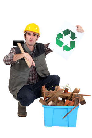 craftsman holding a recycling label and pointing at a box of used materials photo