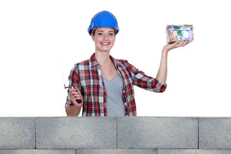 Female in mason clothing holding a house-shaped piggy bank photo