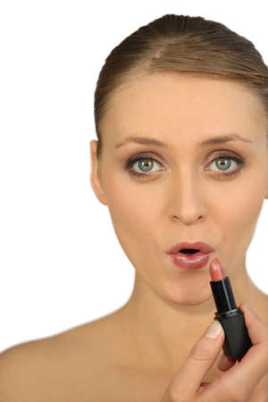 Woman applying lipstick photo